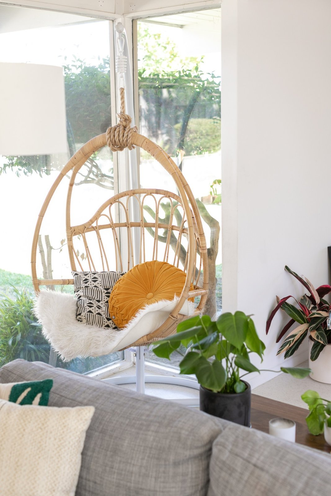 Living Room, Sofa, and Chair A hanging rattan chair is often used as a reading nook.   Photo 4 of 16 in Wellness Guru Joanne Encarnacion's Blissful A-Frame Eichler