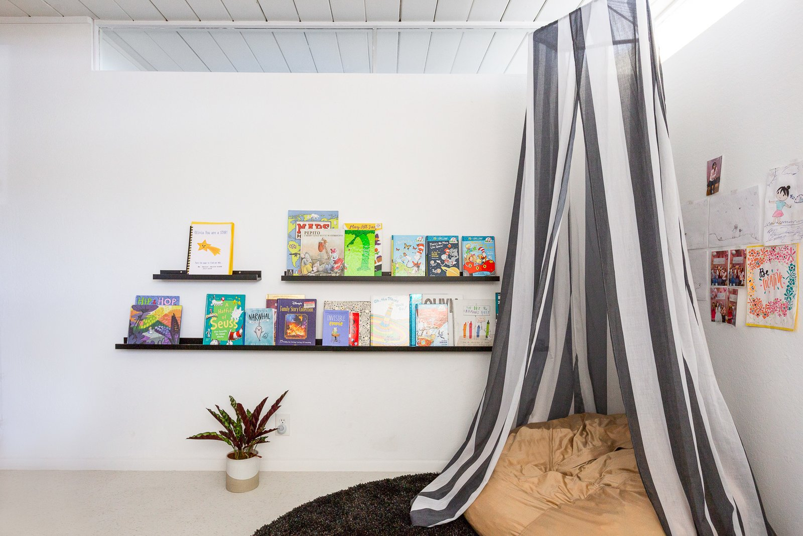 Kids, Rug, Pre-Teen, Shelves, Bedroom, and Girl In 8-year-old Olivia's room, minimalist bookshelves and a comfy hideaway make for the perfect retreat.  Best Kids Bedroom Rug Photos from Wellness Guru Joanne Encarnacion's Blissful A-Frame Eichler