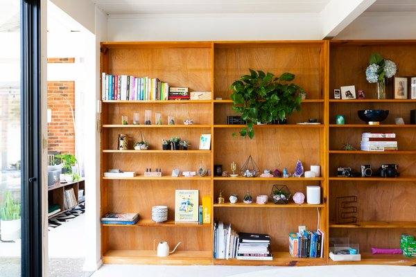 The bookshelf across from the breakfast nook holds favorite books, crystals, plants, and vintage cameras.