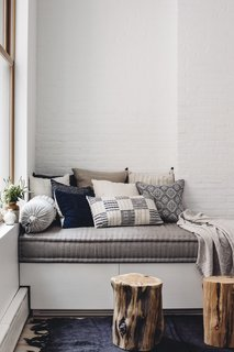 The built-in day bed by JFL Custom Builders provides a cozy corner. Topped with a pillow assortment by Walter G textiles, Bungalow Decor, and Injiri, it's ideal for cuddling up with a book and a blanket. West Elm wood stumps and an antique hemp rug round out the space with some added depth.
