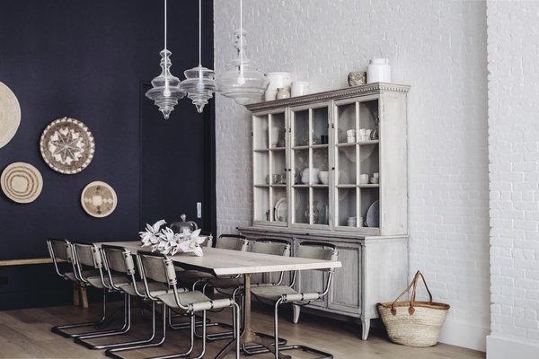 """The dining room melds a modern accent wall swathed in """"Railings"""" paint by Farrow and Ball with hanging wall baskets from Habitat Greenwich, bold pendants by Hudson Valley Lighting, and an antique hutch from Lone Ranger Antiques. In the center sits a dining table, custom created with Studio Endo, and chairs from Sarreid."""