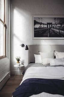 Exposed brick and natural light add a touch of quintessential New York loft  style to the updated home. Restoration Hardware sconces, pillows from Injiri and Susan Connor, and a throw from ABC home tie the room together in the perfect combination of structured and cozy.