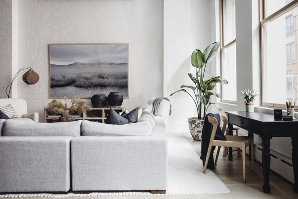The airy living room shows off a monochrome landscape by Petros Koublis framed by an Interior Define sectional and Verellen coffee table. Extra accents include a floor lamp by Bungalow Decor in Westport, block print pillows by Susan Connor, aerrain plant pot, and black urns by Habitat Greenwich. Tying the space together is a rug from Restoration Hardware.