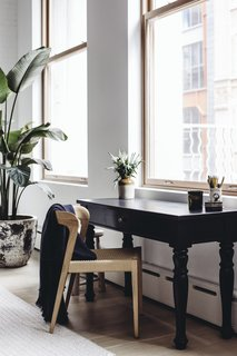 A quiet workspace with black mango wood gear table by Club CU sits in the living room, overlooking the city.