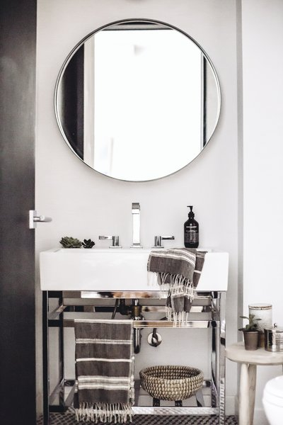 The stone-hued palette makes its way into the powder room where minimalist style is matched with luxurious textiles from Creative Women and silver finishings. A Pottery Barn vanity offers a foundation for a Dornbracht faucet and Grown Alchemist soap.