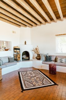 Three kiva fireplaces—and a large collection of rugs and textiles—offer warmth on cold desert nights.