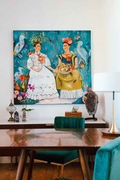 Young's home office exudes rustic glam with a painting of Frida Kahlo, vintage and contemporary lighting, polished and raw stones, and a midcentury table with plush chairs.