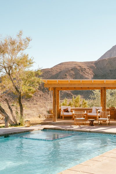 Despite the home's stylish interiors, Young is most drawn to what lies outdoors—a lounge for quiet moments and al fresco dining, a pool, an outdoor shower, the views, a 1972 VW Meyers Manx dune buggy, and a raised adobe platform with a teepee on the back veranda.