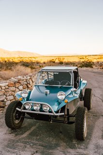 """The buggy is a 1972 VW Meyers Manx dune buggy. We bought it last year and had quite a bit of work done to it so it can handle the rugged desert terrain with ease. We added a new frame, new suspension, new tires, new wiring, and a roll cage. The engine and the body are the only original elements."""