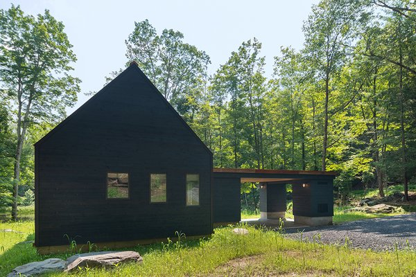 The back of the home and gable ends are covered in blackened cedar.