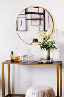 A Safavieh Classic iron console with a Ren-Wil Oryx 30-inch round mirror stands as a chic bar nook.
