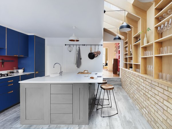 The center island serves as a breakfast nook, sink space, and storage, and marks a transition from bold, blue cabinets into open shelving.