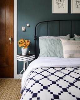 Moody hues penetrate the bedroom, which has deep emerald walls and a Crate & Barrel Mason Shadow bed in black. Francois brightened up the room with a Schoolhouse Winter + Summer cotton coverlet, a Pottery Barn Heather Chenille jute rug, and Matisse prints from Vivid Pictures via Etsy.