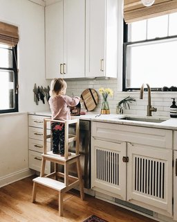 To allow for their two-year-old to be more involved in kitchen happenings, they built a toddler stool. The IKEA stool has a DIY topper frame to keep Sylvia from teetering off.