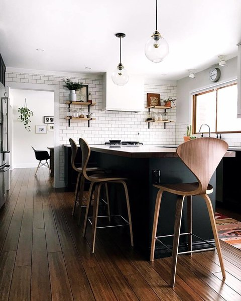 For the kitchen, Conklin did an almost full demolition, adding in new flooring, tearing out cabinets, and adding an island, subway tile, and open shelving. The couple turned to Rejuvenation for the pendant lights and All Modern for the chairs.