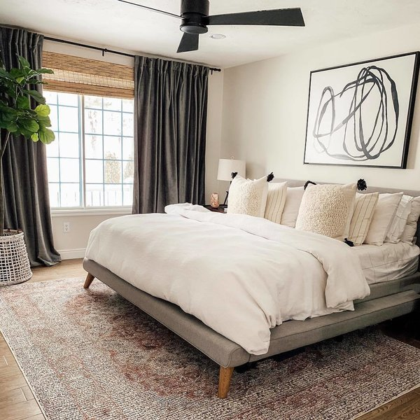 A fresh coat of paint, a new light fixture, and updated decor make all the difference. Julia placed a West Elm Mod Upholstered bed set over a Loloi Rugs Porcia PB-07 rug from Hayneedle. The bedroom is adorned with a Motion Lines 3 print from Anthropologie and worn velvet curtains from West Elm.