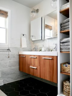 The couple turned a third bedroom into an en suite master bath by knocking down the walls between the two rooms, re-framing and building new walls, and adding plumbing and electrical.