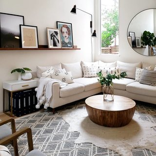 A Sloane Interior Define sofa wraps around the living room with a Jacob coffee table from Wayfair in the center. The Acme Coleen side table in white and brass is from Houzz, and a Talari indigo ottoman from The Citizenry is stashed underneath. Expanding the space is a Glen mirror from Modern Komfort.