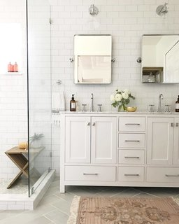 """For the master bathroom, I wanted to create a spa-like retreat for my husband and I. We chose classic finishes with gray herringbone floor tile, white subway tile for the walls, and chrome fixtures and hardware. We also took down a wall that separated the toilet and shower from the sink area and it made the bathroom feel twice as large."""