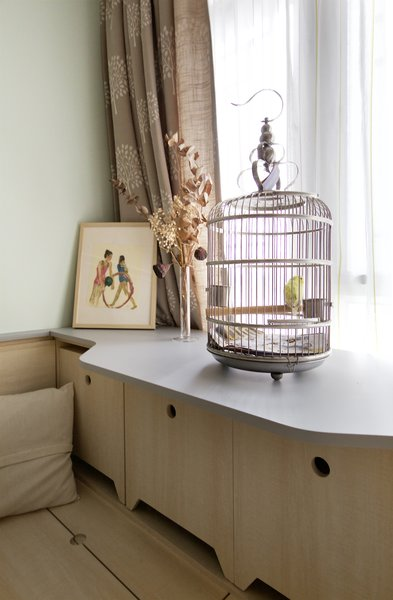 The extra wide cabinet top is specifically designed to hold the cage. Underneath lies extra seating for when the full dining table is rolled out of the kitchen cabinet.
