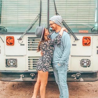 Chase and Mariajosé in front of their bus.