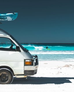 Out catching waves with home parked right on the shore.