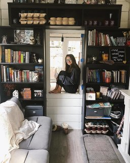 Nicolette perches between bookshelves in the living space.