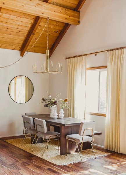 The airy dining room is swathed in sunny hues. A Rejuvenation Sumac flatweave rug in Marigold lays the foundation with a West Elm Hayes table set and Wire Frame dining chairs. Shade Store drapes in Ecru add to the gilded nature of the space, while a Brigitte chandelier by Mitzi hangs overhead.