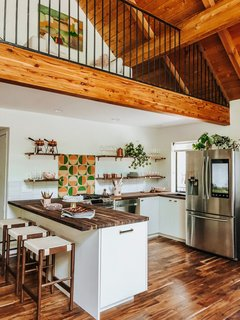 "Thomas transformed the kitchen from an ""awkward, closed-off space"" into an airy cook's corner where loved ones can congregate. Thomas put in high-end, smart appliances (the refrigerator connects to Instacart), swapped upper cabinets for open shelving, and repainted and reconfigured the space to an L-shape to fit a row of Shaw stools in walnut from Rejuvenation. The cabinets are all IKEA with Semihandmade doors in Slab Antique, while counter tops and floating shelves are from Limber Liquidators, with brass strap brackets by Rejuvenation. ""All of this is tied together with a giant wallop of color by Fireclay Tile. I chose a blend of saffron, avocado, and sorbet pink as my color cues throughout the cabin, and these custom handmade tiles are just so joyful and unexpected."""
