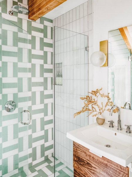 "Thomas loves crazy powder rooms, but leans towards softer tones for master bathrooms. Here, she adds a bit of glam with chrome Atrio fixtures by Grohe and antique brass Hinsdale sconces by Hudson Valley Lighting. ""I am so happy with how this midcentury-inspired pattern using Fireclay Tile in Daisy and Sea Glass turned out. It's dramatic, but still soothing and soft. The sconces reminded me of modernist versions of soap bubbles, and I loved them for a bathroom environment."""