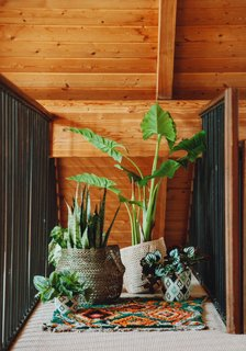 """""""Just as you come up the stairs, there's a small catwalk, and for some reason I instantly knew I wanted a little jungle of plants there. I used a variety of Little Market baskets on top of the cutest little green carpet by Coco Carpets."""""""