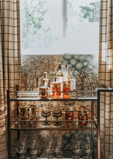 """""""I felt like an epic bar cart needed to make an appearance somewhere, and the den-like quality of the game room felt like just the place. I used the Brixton bar cart from Room & Board and filled it with some of my favorite vintage pieces as well as some new ones from West Elm. The copper Moscow Mule mugs are necessary for a cabin weekend."""""""