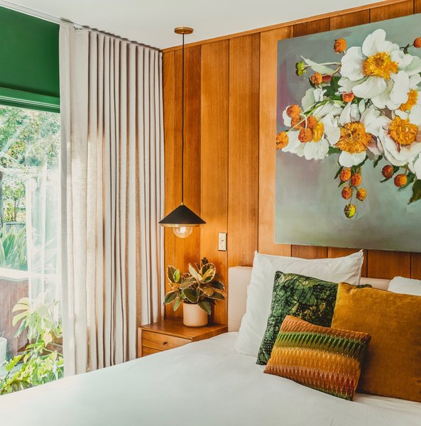 """""""I love the view from our bed, and had this idea of bringing the outside in through color,"""" says Thomas. """"I painted the room a rich, emerald green—Mission Jewel by Dunn Edwards—and centered the color palette on a painting by Michael Harnish of a floral arrangement by my dear friend, Yasmine Khatib."""" Black-and-brass Mitzi pendants float above the nightstand, while two chairs she reupholstered with Kravet velvet sit in the corner to match the dark walls. Floor-to-ceiling drapes by The Shade Store add a touch of drama."""