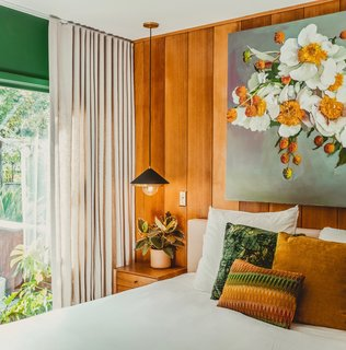 """I love the view from our bed, and had this idea of bringing the outside in through color,"" says Thomas. ""I painted the room a rich, emerald green—Mission Jewel by Dunn Edwards—and centered the color palette on a painting by Michael Harnish of a floral arrangement by my dear friend, Yasmine Khatib."" Black-and-brass Mitzi pendants float above the nightstand, while two chairs she reupholstered with Kravet velvet sit in the corner to match the dark walls. Floor-to-ceiling drapes by The Shade Store add a touch of drama."