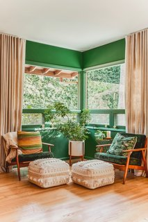 The green hue permeates her space, including this boho sitting area.