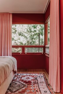 A Rejuvenation rug, drapes from The Shade Store, and bedding from Parachute all echo the rust and pink palette.