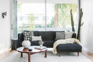 The living area features a classic, black-and-white palette, including Ziggy Nesting Tables from Guest House.