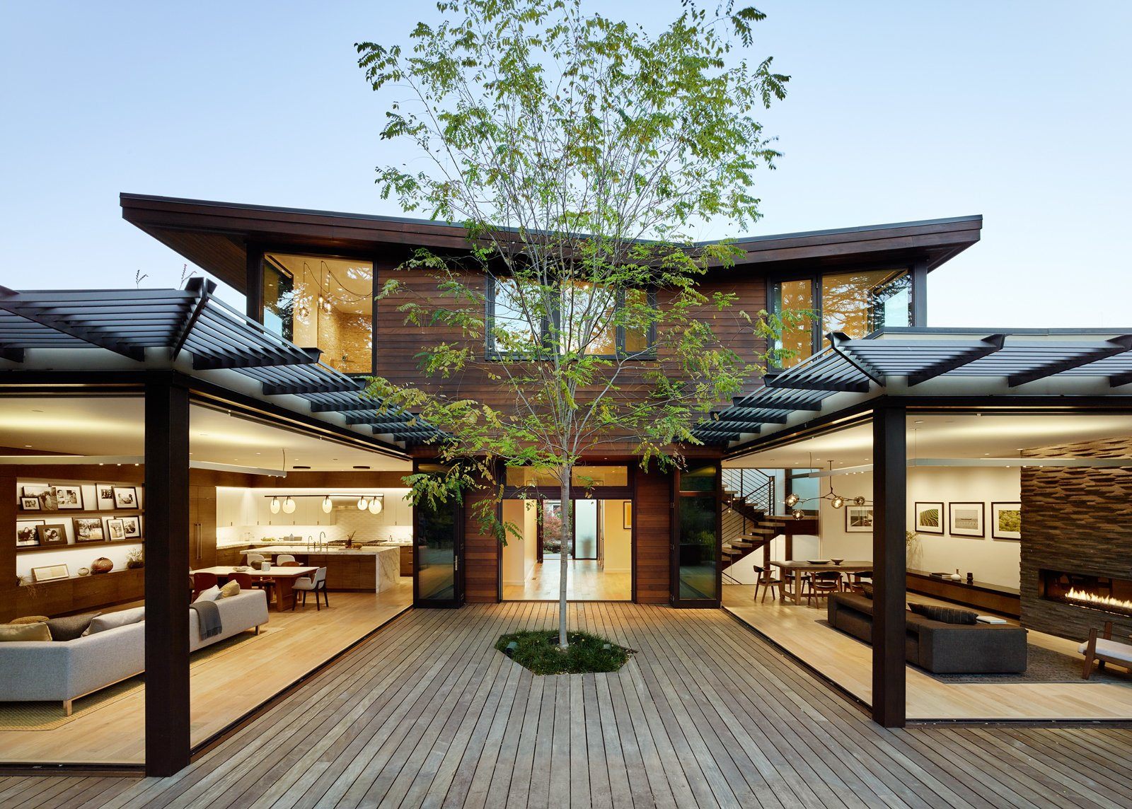 Outdoor, Large Patio, Porch, Deck, Decking Patio, Porch, Deck, Trees, Wood Patio, Porch, Deck, and Back Yard A single tree in the courtyard anchors the central space.  Photo 11 of 13 in A Silicon Valley Retreat Sports a Butterfly Roof and Two Indoor/Outdoor Wings