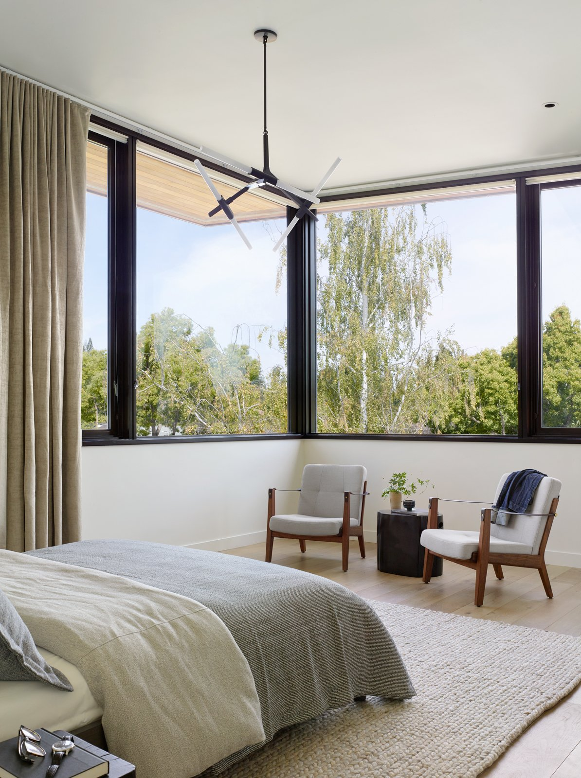 Bedroom, Bed, Rug Floor, Ceiling Lighting, Light Hardwood Floor, and Chair The airy second floor of the home opens up to treetops all around.  Photo 10 of 13 in A Silicon Valley Retreat Sports a Butterfly Roof and Two Indoor/Outdoor Wings