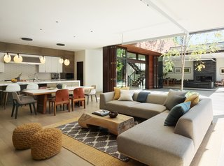A Dellarobia Sectional offers comfy seating in the casual living room with a coffee table by Buka Design + Hardwoods.