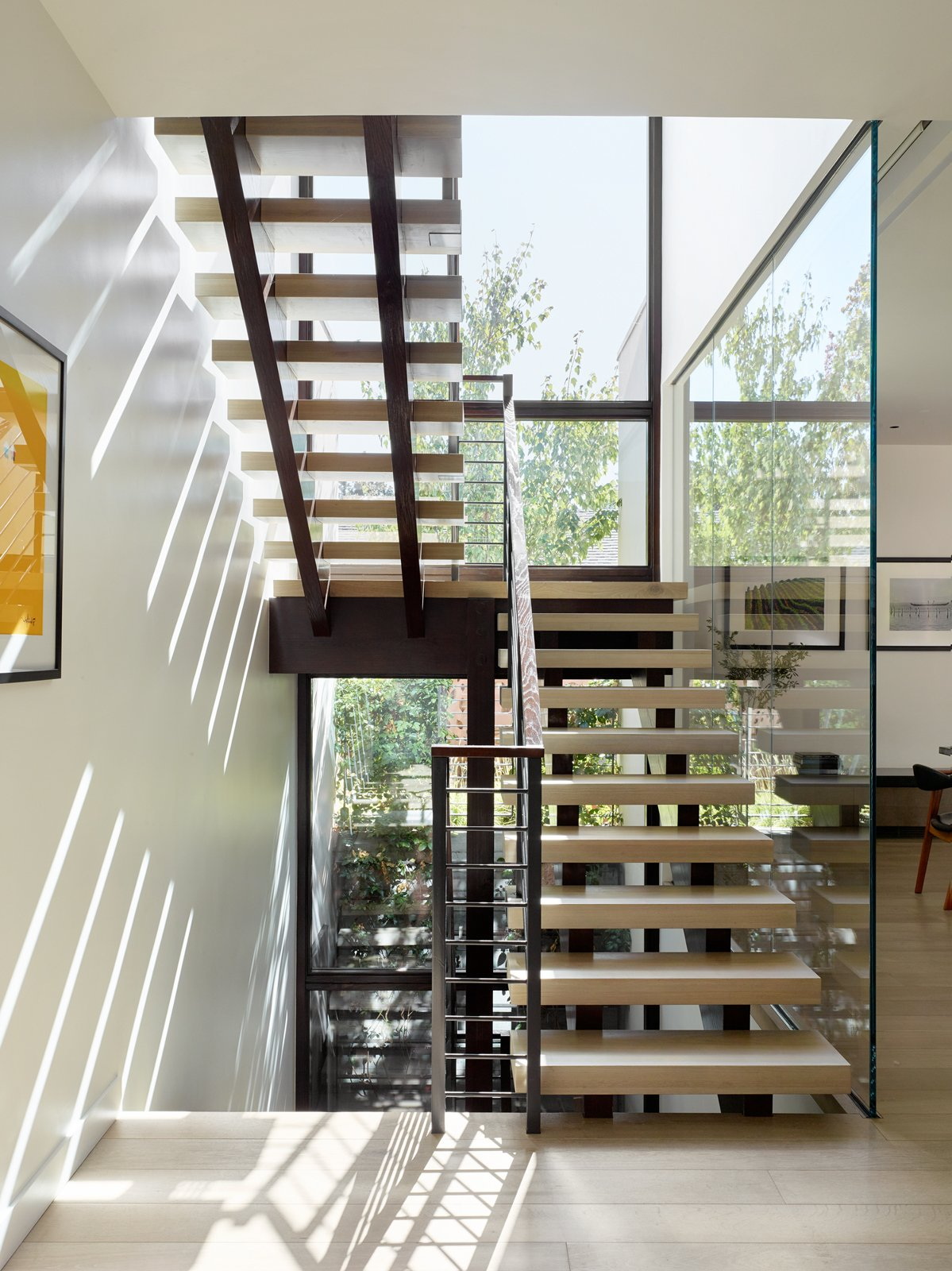 Staircase, Metal Railing, and Stone Tread An open central stair located next to a building-high glass wall makes traveling between floors a dynamic experience.  Photos from A Silicon Valley Retreat Sports a Butterfly Roof and Two Indoor/Outdoor Wings