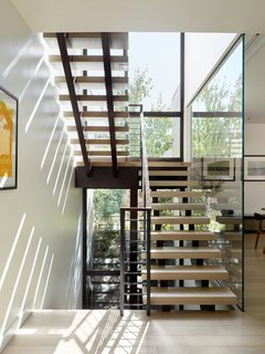 An open central stair located next to a building-high glass wall makes traveling between floors a dynamic experience.