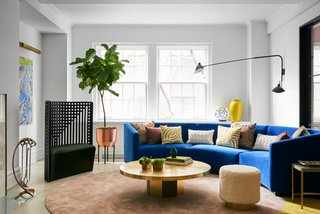 The wood herringbone floors were lightened, and bold furniture was brought in to brighten up the space. A circular custom sofa designed by MKCA, upholstered in a bright blue synthetic textile from Maharam, serves as the centerpiece of the room, readily available for family time, intimate conversation, or parties. Surrounding a vintage brass table are a sculptural chair by Charles Rennie Mackintosh and poufs upholstered in shaggy mohair.  The carpet by MKCA is made from joining two shapes of broadloom synthetic silk together.