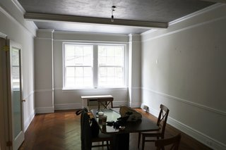 The dining room was drab with plain walls, dark flooring, and a single bulb jutting out of the ceiling.