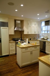 The kitchen was outdated with yellowed stone counters, bulky cabinets and appliances, and dark flooring.