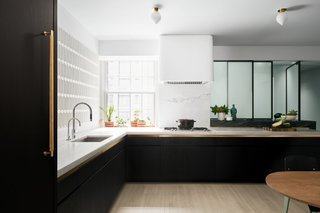 Chen used high-contrast materials to lighten the space, which has only one window. He lined the kitchen in glossy 3-D tile from Ann Sacks, and wall covering from Flat Vernacular. He removed the rear wall of the kitchen and replaced it with a sliding acid-etched glass partition, which picks up ambient light from windows in the service entrance. Chen installed drawers below the white marble countertops and swapped out overhead cabinets for full-height cabinets in the pantry. Under the glass partition, a thick counter of striped Kenya Black marble adds doubles as a bar top and work surface.