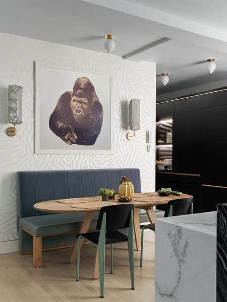 An Enzo Mari gorilla print hangs over the breakfast table, flanked by Erich Ginder fabric sconces. Overhead, a handful of Michael Anastassiades fixtures from The Future Perfect offers ample task lighting.