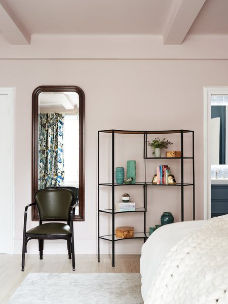MKCA painted the bedroom a muted pink and added custom-milled his and hers closets and new finishes and fixtures in the master bath. A vintage shelving unit by Frederick Weinberg sourced from eBay holds ceramics and books that the couple collect, and the bed is flanked by vintage nightstands by Luigi Caccia Dominioni for Azucena, sourced from Compasso Gallery. The custom sconces are by Allied Maker.