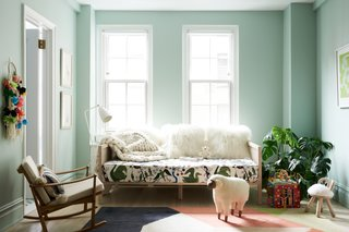 MKCA removed the carpet and cabinetry and repainted the walls to polish the room. Tropical motifs from the front of the apartment mingle with Scandinavian sensibilities. Sheepskin pillows add softness to a CB2 daybed with a custom cushion, upholstered in a Josef Frank botanical print. A vintage teak rocker by Finn Juhl, tall shelving from Hem, and a coterie of animal-cum-footstool pieces from Kinder Modern surround the daughter's play table.