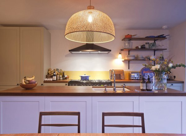 A bamboo pendant from Wonen Met Lef hangs over the kitchen island.